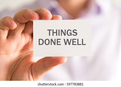 Closeup on businessman holding a card with THINGS DONE WELL message, business concept image with soft focus background