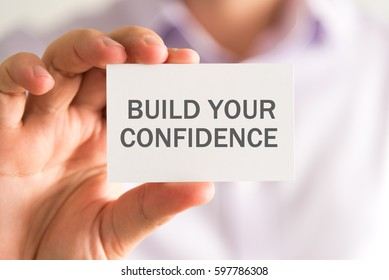 Closeup on businessman holding a card with BUILD YOUR CONFIDENCE message, business concept image with soft focus background