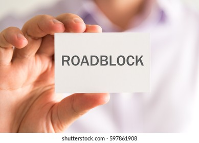 Closeup on businessman holding a card with ROADBLOCK message, business concept image with soft focus background