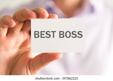 Closeup on businessman holding a card with BEST BOSS message, business concept image with soft focus background