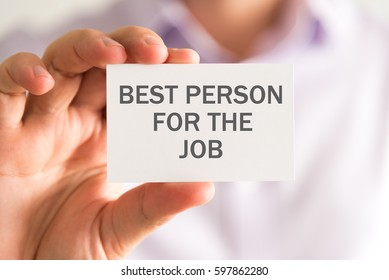Closeup on businessman holding a card with BEST PERSON FOR THE JOB message, business concept image with soft focus background