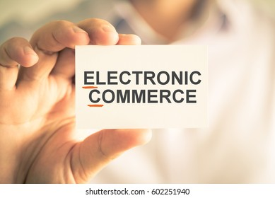 Closeup on businessman holding card with EC ELECTRONIC COMMERCE acronym text, business concept image with soft focus background and vintage tone