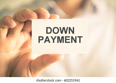 Closeup on businessman holding a card with text DOWN PAYMENT, business concept image with soft focus background and vintage tone