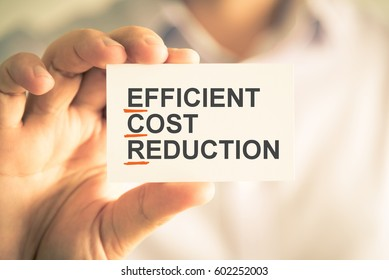 Closeup on businessman holding card with ECR EFFICIENT COST REDUCTION acronym text, business concept image with soft focus background and vintage tone