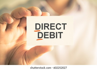 Closeup on businessman holding card with DD DIRECT DEBIT acronym text, business concept image with soft focus background and vintage tone