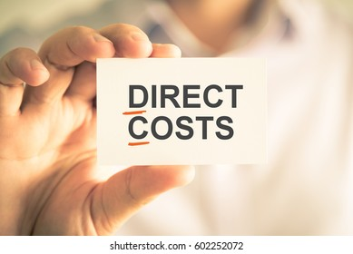 Closeup on businessman holding card with DC DIRECT COSTS acronym text, business concept image with soft focus background and vintage tone