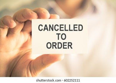 Closeup on businessman holding a card with text CANCELLED TO ORDER, business concept image with soft focus background and vintage tone