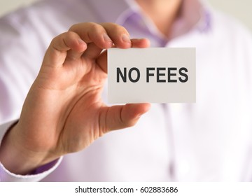 Closeup on businessman holding a card with NO FEES message, business concept image with soft focus background