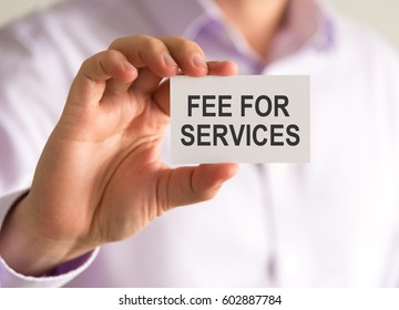 Closeup on businessman holding a card with FEE FOR SERVICES message, business concept image with soft focus background