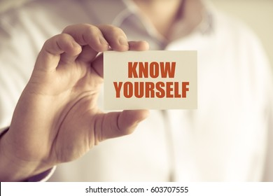 Closeup on businessman holding a card with text KNOW YOURSELF, business concept image with soft focus background and vintage tone