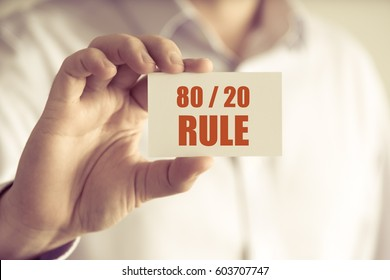 Closeup on businessman holding a card with text 80 20 RULE, business concept image with soft focus background and vintage tone