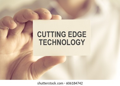 Closeup on businessman holding a card with text CUTTING EDGE TECHNOLOGY, business concept image with soft focus background and vintage tone