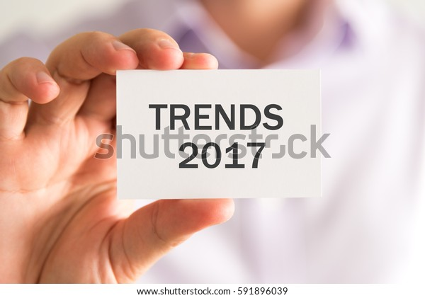 Closeup on businessman holding a card with TRENDS 2017 message, business concept image with soft focus background