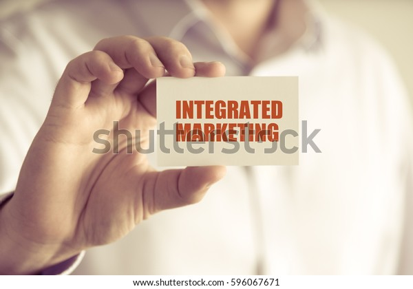 Closeup on businessman holding a card with text INTEGRATED MARKETING, business concept image with soft focus background and vintage tone