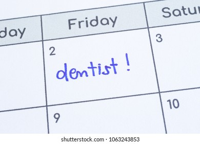 Closeup on calendar page, focus on blue handwriting the word Dentist written on timetable date 2nd under Friday column. Appointment note health reminder, schedule, personal time management.