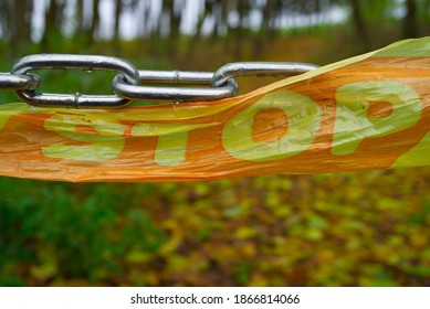 Close-up on chain barrier with stop sign on plastic tape in the woods. End of road or private property concept