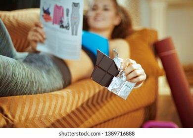 Closeup on chocolate bar in hands of fit woman laying on sofa with magazine in the modern living room.