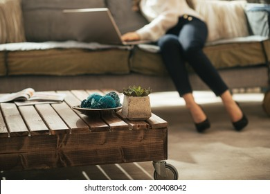 Closeup on coffee table and young woman using laptop in background