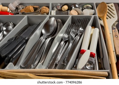 Close-up on on the contents of a kitchen drawer full of cutlery and utensils