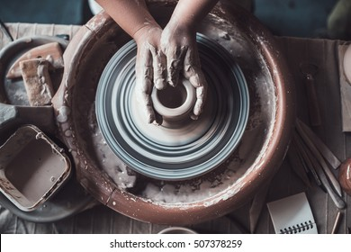 Close-up on creativity. Top view of potter making ceramic pot on the pottery wheel