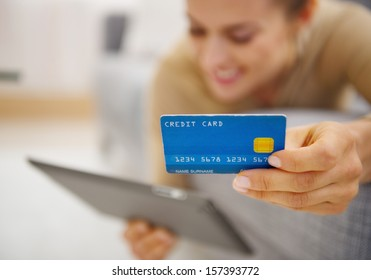 Closeup on credit card in hand of young woman laying on couch with tablet pc