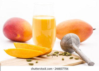 Close-up on crushed cardamon seeds and cut mango fruit pulp on a wooden cutting board. A metallic pestle and two whole mangos. Domestic kitchen scene. White background. Selective focus. Low angle.