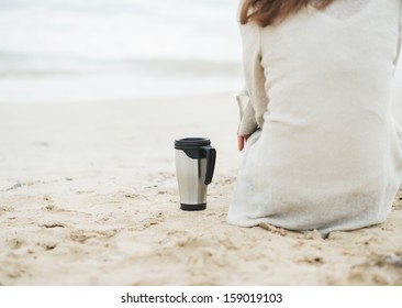 Closeup on cup of hot beverage near young woman in sweater sitting on lonely beach