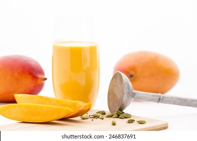 Closeup on cut mango pieces and crushed cardamom seeds. Both main ingredients for a refreshing mango mocktail. Two whole mangos and a metal pestle. Selective focus. White background. Low camera angle.