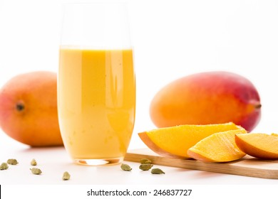 Close-up on cut mango pieces on a wooden cutting board. A glass filled with mango lassi, cardamom seeds and two entire mangos. Selective focus. Low angle shot. White background and bright table top.