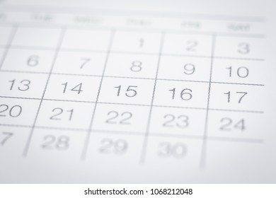 Closeup on dates of simple calendar page. Selective focus shown dot prints, blurred area on top and bottom. Black and white tone with modern minimal style. Work appointment, reminder and timetable.