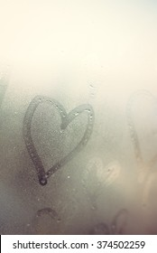 Closeup on drawing love hearts on wet window background