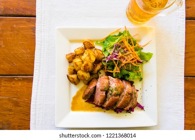 Close-up on duck breast and potatoes dish with cold beer in background