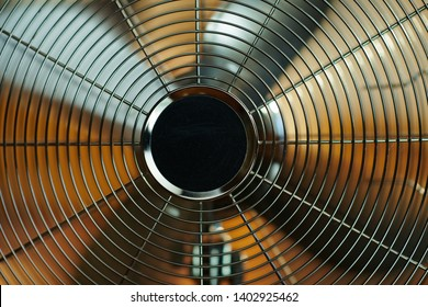 Closeup on electric metallic fan in the modern house in sunny hot summer day.