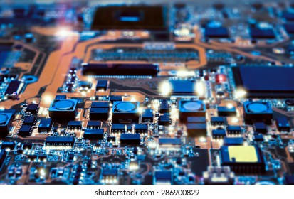 Closeup on electronic board in hardware repair shop, blurred and toned image. Shallow DOF, focus on the middle left field