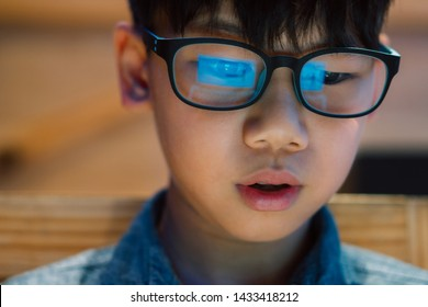 Closeup on face - smart look Asian preteen/teenage boy staring at computer laptop screen with concentration and excitement, wearing blue light blocking glasses. Reflection of computer screen, Student.