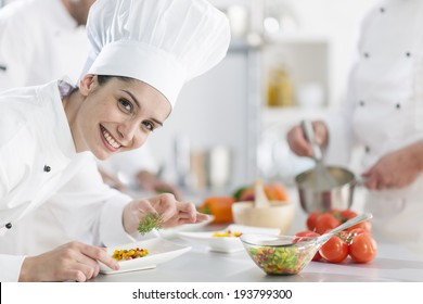 closeup on a  female chef preparing a dish her team in the background