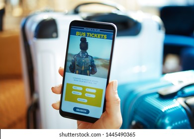 Closeup on female hand with smartphone near trolley bags at modern home in sunny hot summer day booking bus tickets online using app.