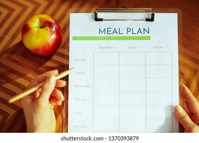 Closeup on female hands holding clipboard and filling meal plan in the modern house.