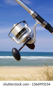 Close-up on fishing reel with beach and ocean in background