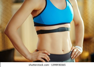 Closeup on fit sports woman in fitness clothes at modern home wearing heart rate monitor.
