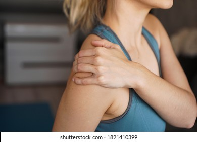 Closeup on fitness woman having pain in shoulder. Pain after home workout