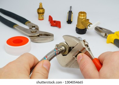 closeup on flexible water supply tubes and adjustable wrench on white background, suitable for header or banner