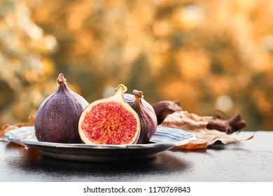 Closeup on fresh figs on dark shiny stone plate outdoors, toned image