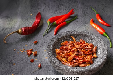 Closeup on  fresh hot chili peppers on dark textured table and dry ones in stone bowl ready for grinding