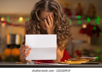 Closeup on frustrated young housewife with letter in christmas decorated kitchen