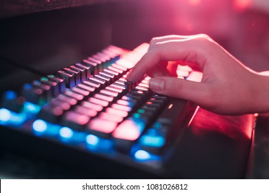 Close-up On Gamer's Hands on a keyboard, Actively Pushing Buttons, Playing MMO Games Online. Background is Lit with Neon Lights.