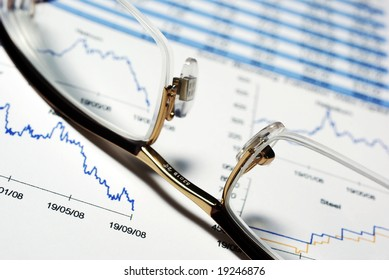 Closeup on glasses and financial report with charts and data.