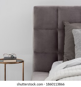Close-up on gray quilted bed headboard and round, golden bedside table in white wall bedroom