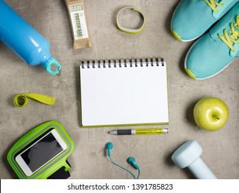 Closeup on green apple, dumbbell, headphones, elastic band, raw protein bar, sneakers, fitness tracker, bottle of water, smartphone in running armband and opened notebook with pen laying on the floor.
