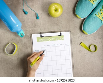 Closeup on green apple, headphones, elastic band, sneakers, fitness tracker, bottle of water laying on the floor and female hand filling workout plan on clipboard with pen.